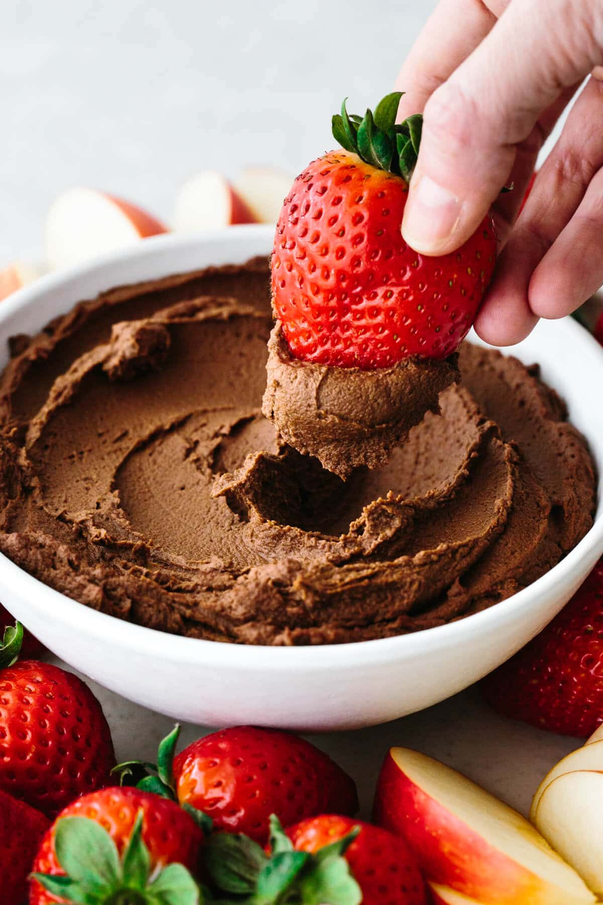 Dipping a strawberry into chocolate hummus.