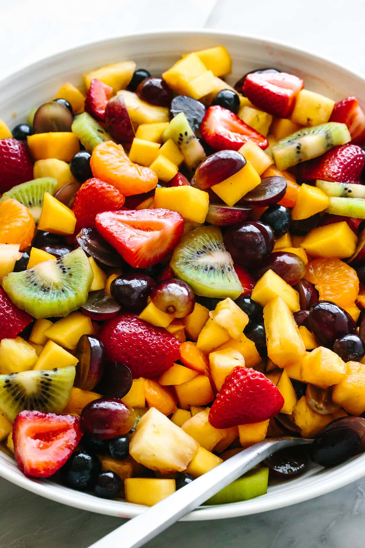A large bowl of fruit salad with a spoon.
